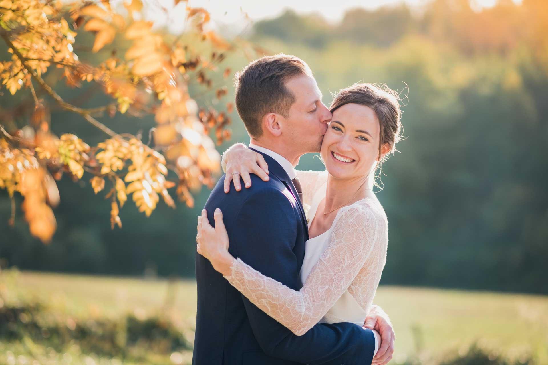 Mariée heureuse embrassée par son mari dans un cadre champetre avec de jolies couleurs d'automne dans les arbres