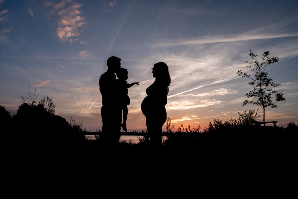 Silhouette d'une femme enceinte d'un homme et d'un enfant sur fond de coucher de soleil à Tournefeuille