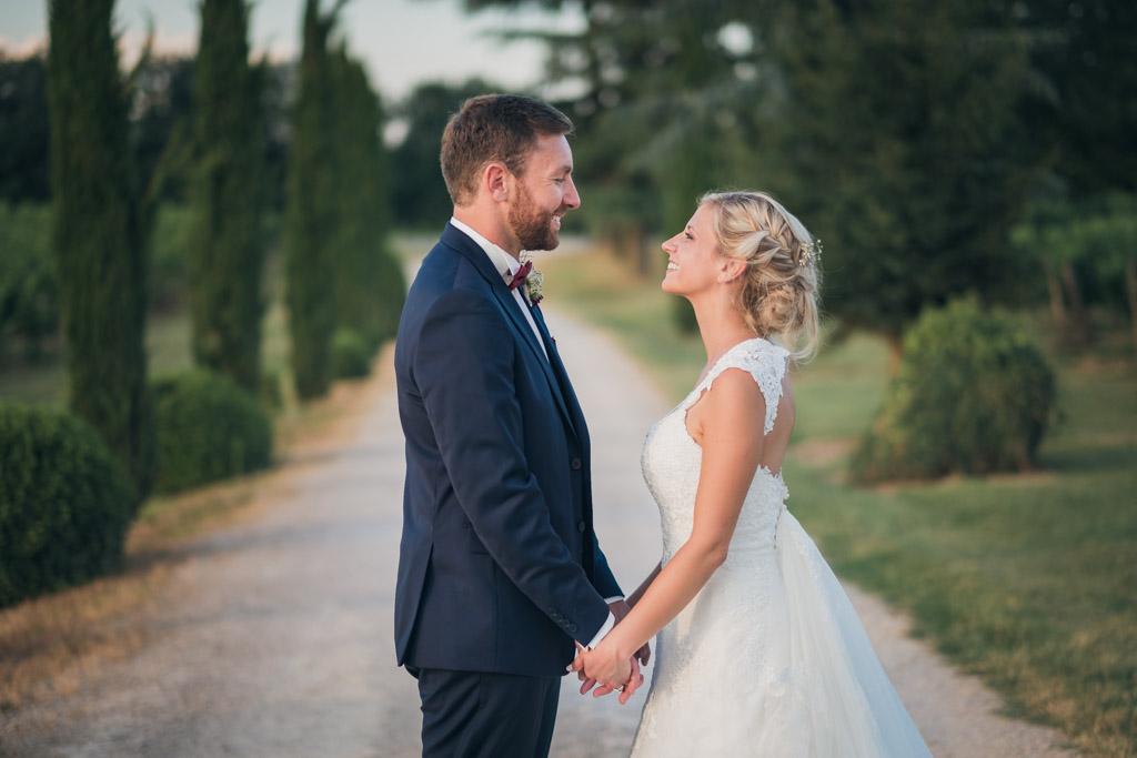Les mariés se regardent dans l'allé menant au domaine du chateau de Terride, main dans la main