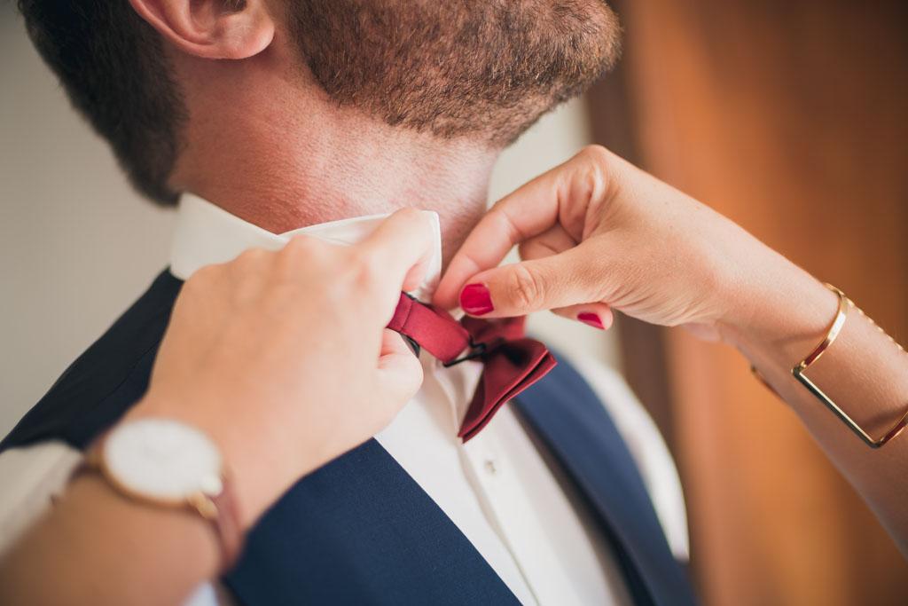 Gros plan sur le nœud papillon bordeaux du futur marié en plein préparatifs