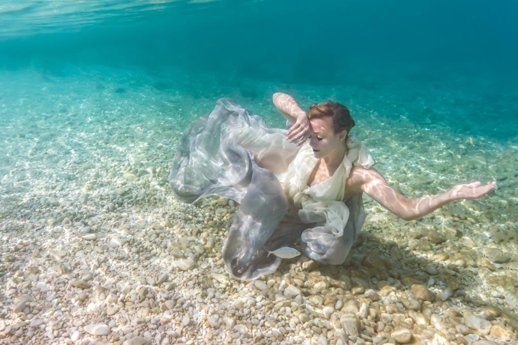 Mariée en robe sous l'eau turquoise et fond marin de sable blanc