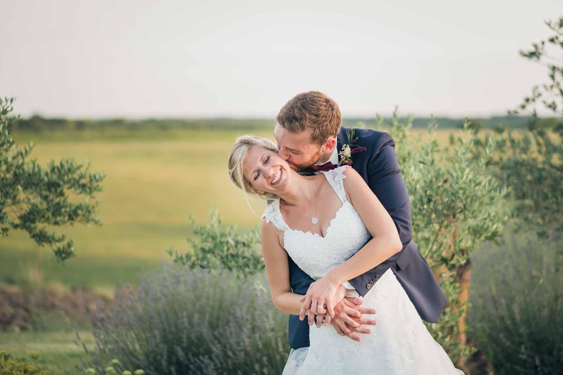 Marié qui embrasse sa femme dans le cou devant des lavandes