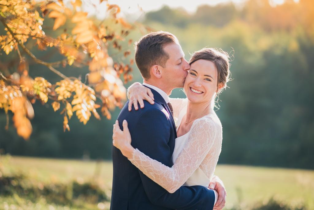 Mariée radieuse embrassée par son mari dans un cadre champetre avec de jolies couleurs d'automne dans les arbres