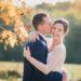 Le marié fait un bisou sur la joue de sa femme souriante et radieuse au milieu des arbres avec des feuilles jaunes d'automne